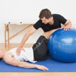 Physical therapist assisting young man with yoga ball in the gym
